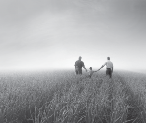 Two people walking with a child in a field