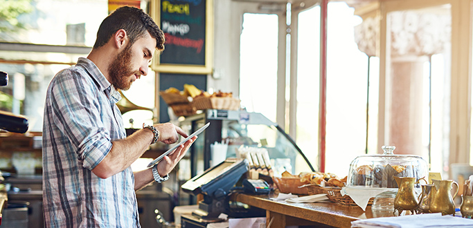 a small business owner works on a tablet behind the counter
