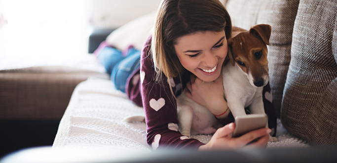 A women lays with her dog while looking at her phone