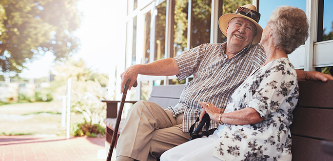 Retiree couple sit on a bench smiling at each other