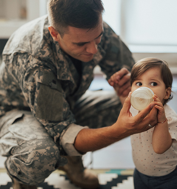 A military Father Feed his baby with a bottle