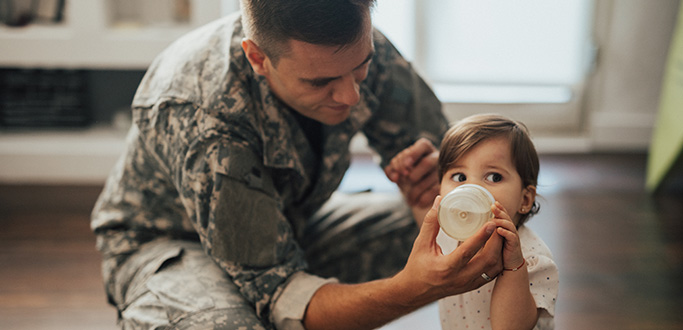 Father in Army fatigues feeding baby with bottle