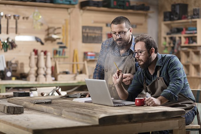 Two woodworkers work on the laptop in their wood shop