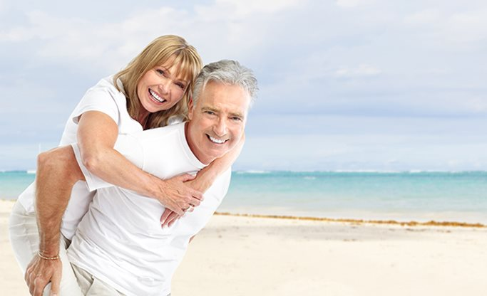 A elderly couple pose smiling on the beach