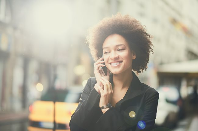 A women smiling while talking on the phone