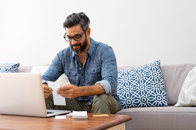 Man holding receipts while scrolling the computer